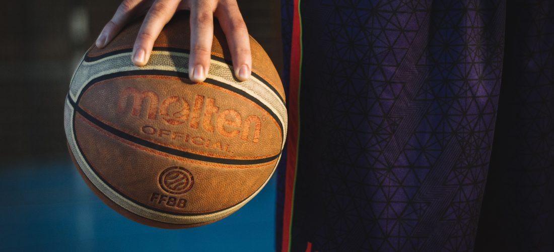 Ein Sportler hält einen Basketball