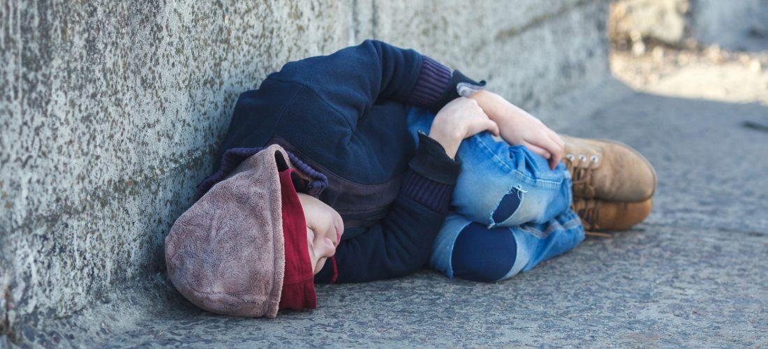 ein obdachloses Kind liegt auf der Straße