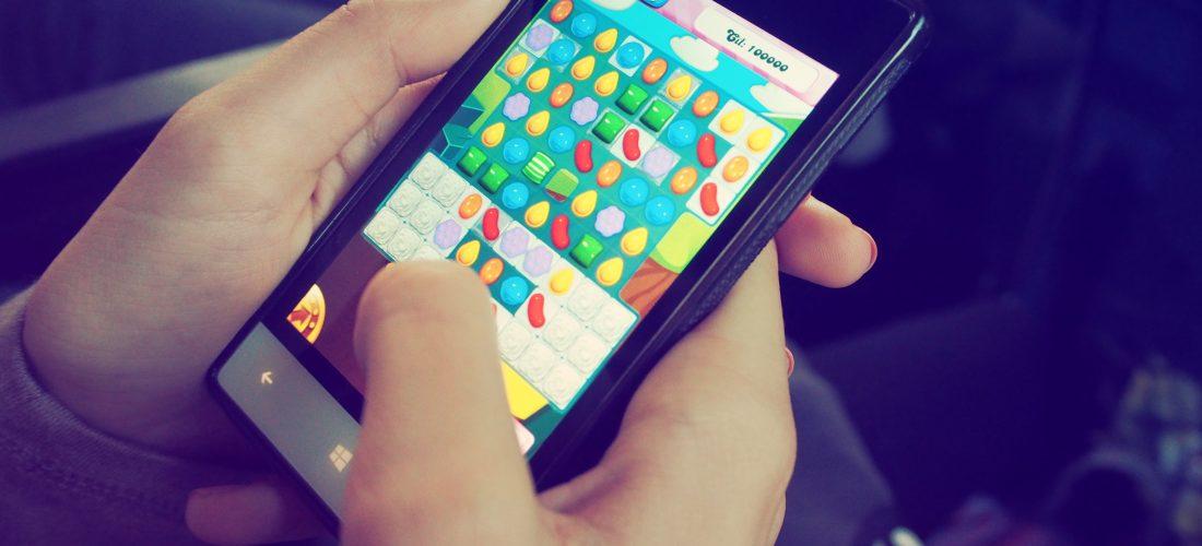 Eine Jugendliche spiel CandyCrush auf dem Smartphone