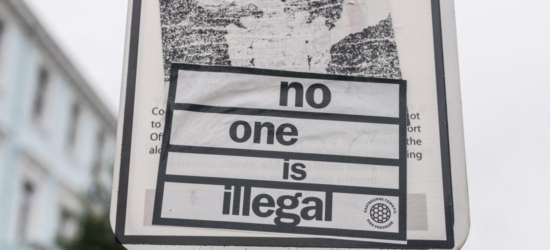 """Straßenschild mit Aufkleber """"no one is illegal"""""""