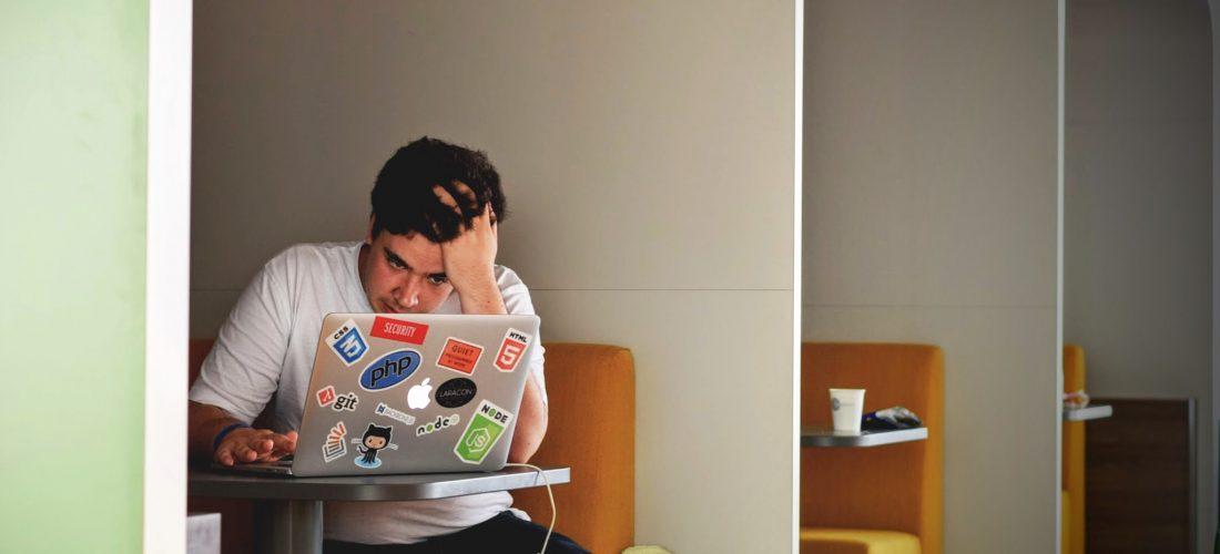Ein Student sitzt am Laptop in der Bibliothek