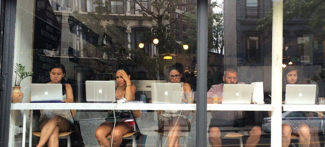 Menschen sitzen im Fenster eines Cafés am Computer