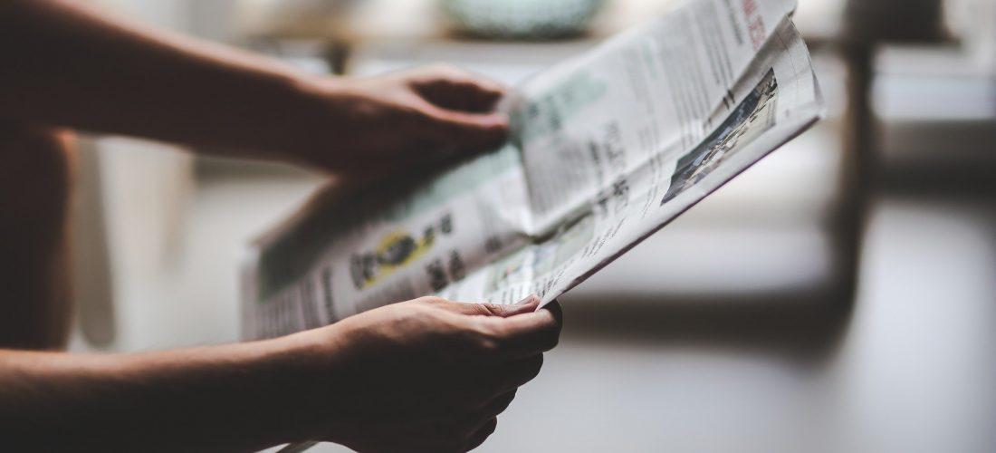 Person hält eine Zeitung in der Hand