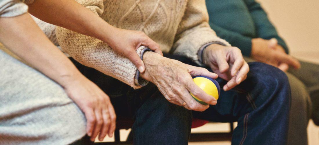 Ein junger Mensch kümmert sich um einen Senioren