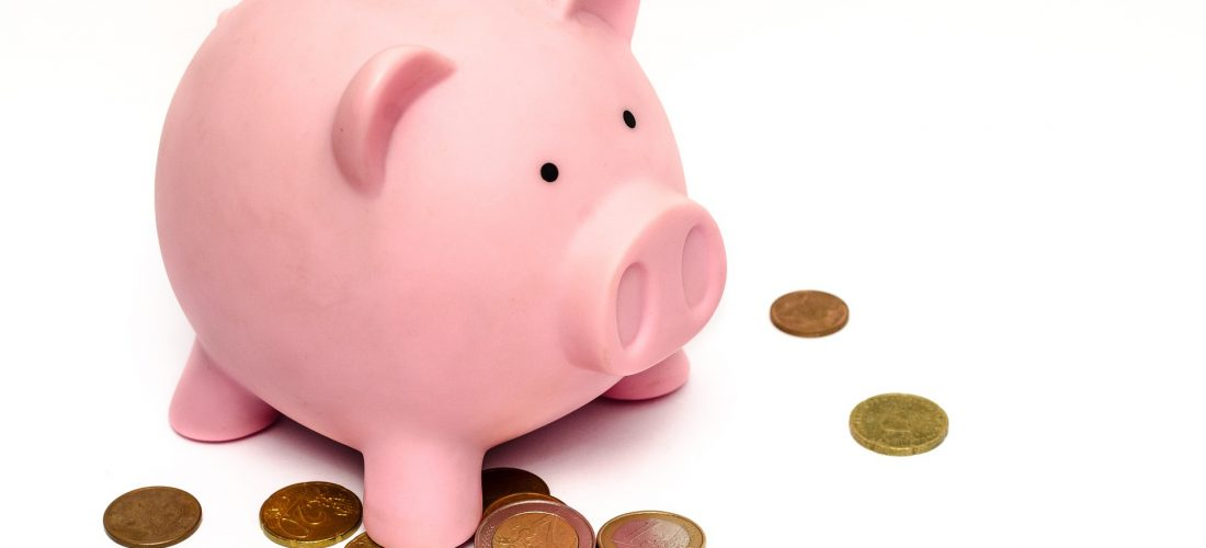 Ein Sparschwein steht auf Euromünzen