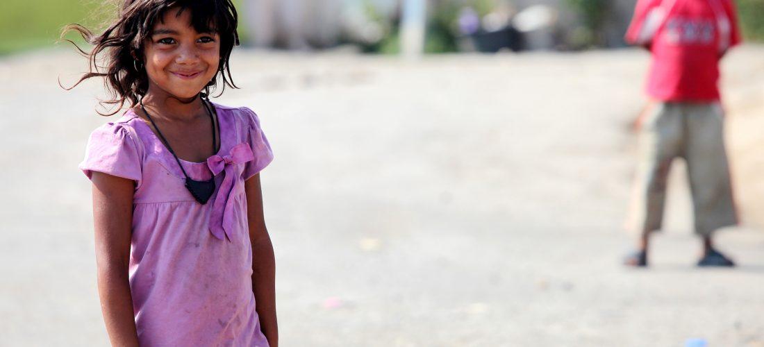 ein kleines Mädchen steht auf einem Platz und lächelt in die Kamera