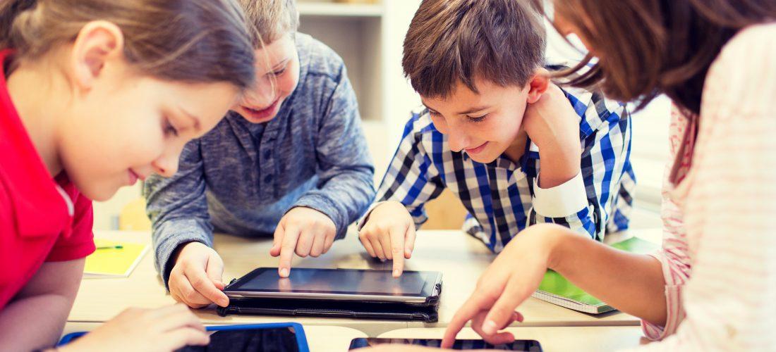 Grundschulkinder spielen mit Tablet-Computern