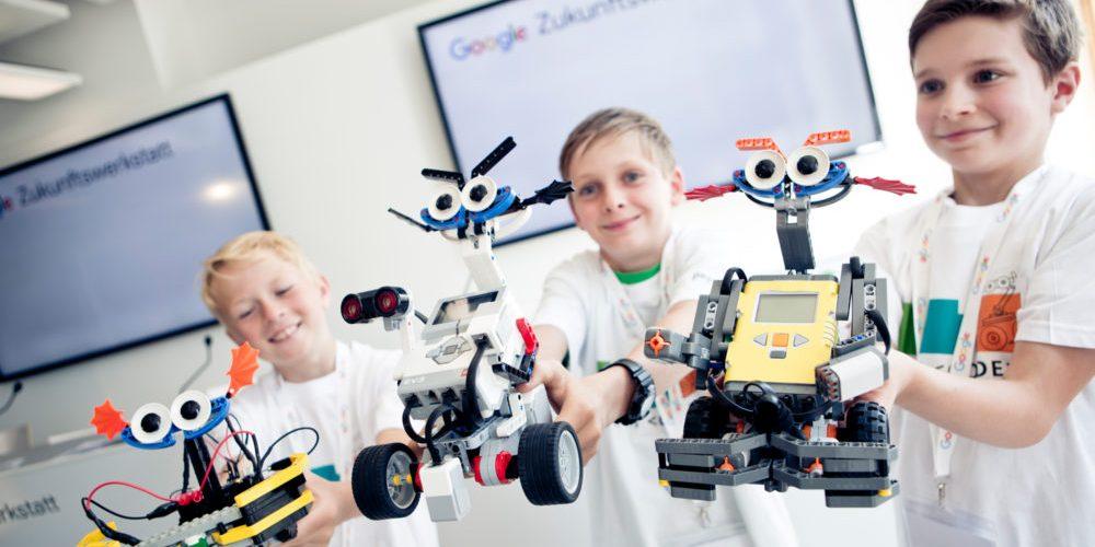 Drei Schüler zeigen stolz ihre Roboter