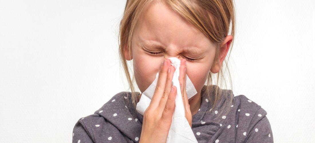 ein kleines Mädchen putzt sich die Nase