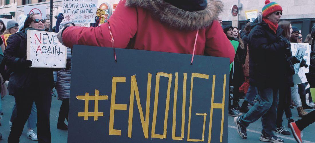 Eine junge Frau trägt während einer Demonstration ein Pappschild mit der Aufschrift #ENOUGH