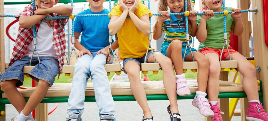 Kinder sitzen auf einem Spielplatz auf einer Hängebrücke