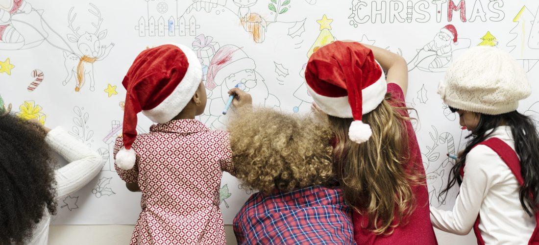Kinder malen eine Wand mit Weihnachtsmotiven aus