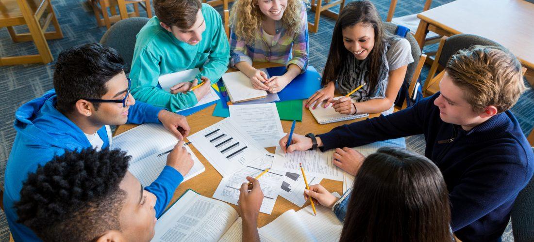 Eine Gruppe Schüler sitzt am Tisch und diskutiert