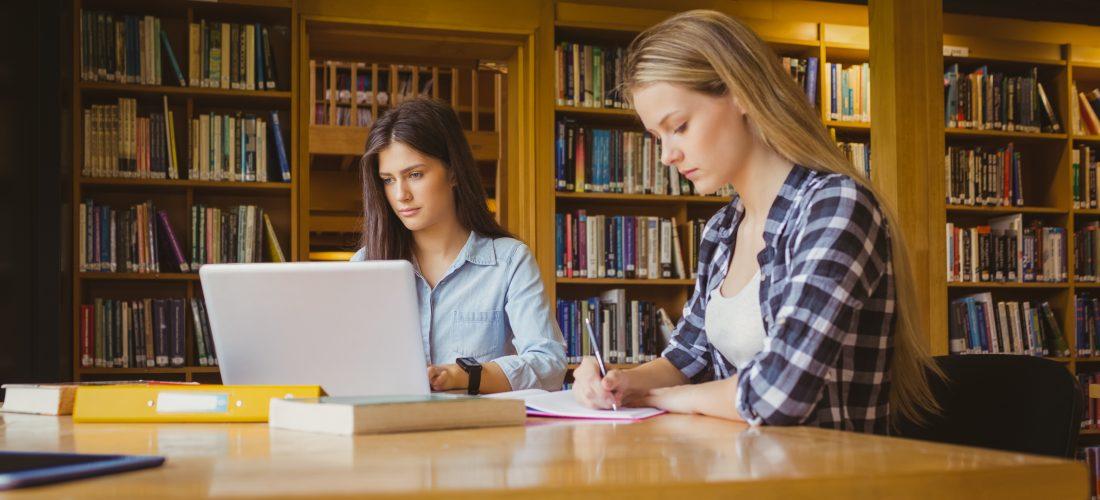 Schülerinnen lernen in einer Bibliothek