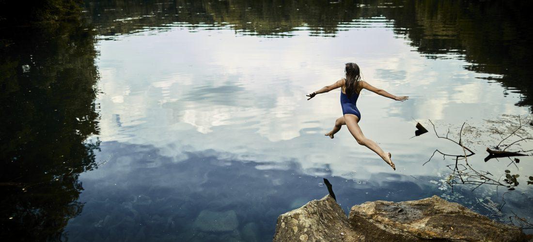 Mädchen springt in einen See