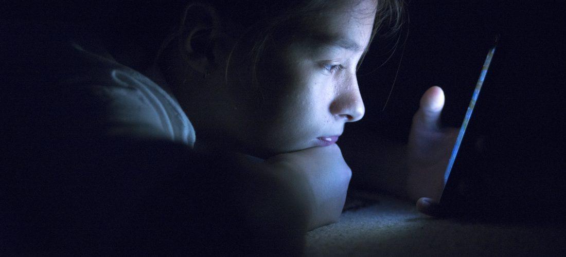 Mädchen schaut im Dunkeln aufs Hand