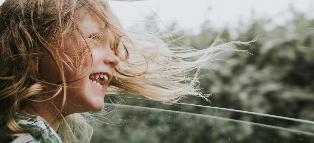Ein Mädchen, deren Haare im Autofahrtwind wehen