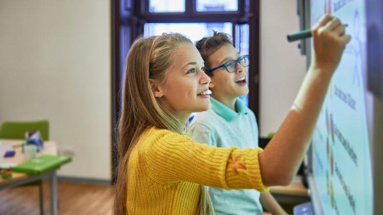 Schüler:in arbeiten an einem Smartboard